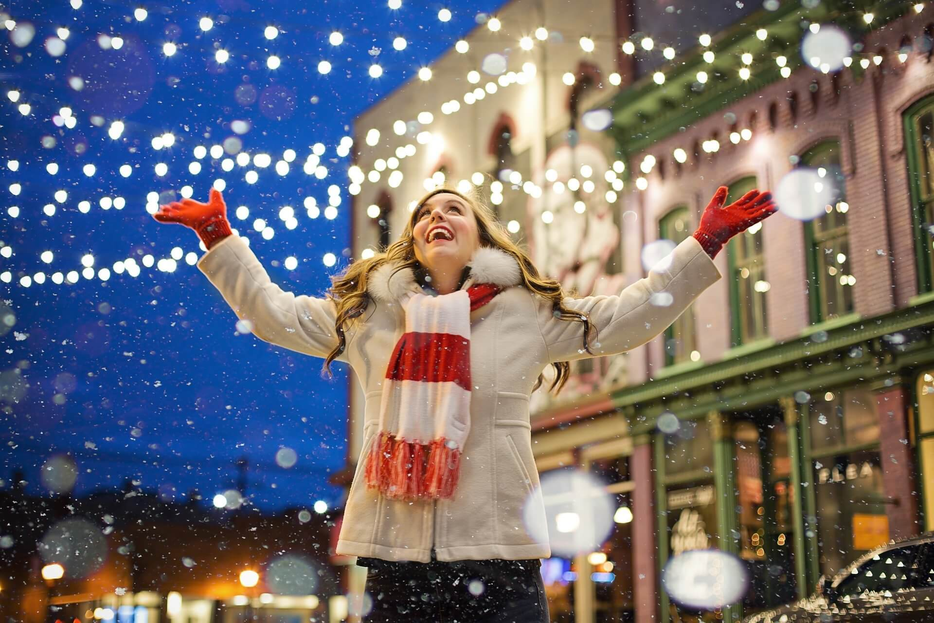 Woman stands outside in the snow in a Christmas decorated street