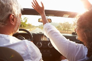 Older couple drive care-free in convertible