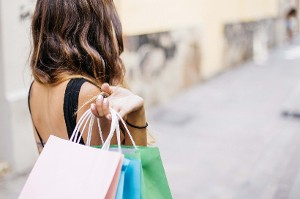 Woman faces away from camera, holding shopping bags