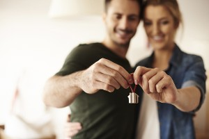 Young couple hug and hold miniature house towards camera